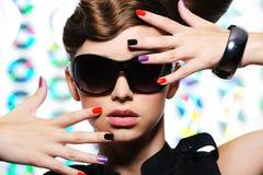 Woman with fashion manicure and stylish sunglasses. Adult woman with fashion multicolored manicure and female stylish sunglasses - close-up Stock Photo