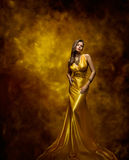 Woman Fashion Model Gold Dress, Beauty Girl in Glamour Gown. Posing on Golden artistic background royalty free stock images