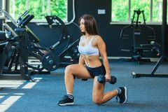 Woman In Fashion Sports Clothes Training, Doing Lunges Exercise with dumbbells in the gym.  royalty free stock images