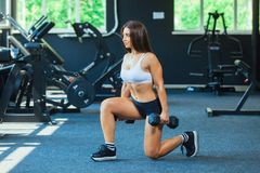 Woman In Fashion Sports Clothes Training, Doing Lunges Exercise with dumbbells in the gym.  royalty free stock photography