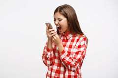 Woman in fashion spring look screaming at phone looking mad. Beautiful woman in dress screaming at phone looking mad and frustrated isolated on white background Stock Images