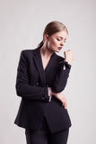 Woman in fashion suit on grey background Royalty Free Stock Photo