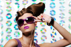 Woman in the fashion sunglasses with hairstyle. Studio portrait of beautiful young girl in the fashion sunglasses with creative hairstyle Royalty Free Stock Image