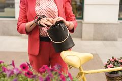 A woman in fashionable clothes of the color of the year 2019 living coral holds in hands with French manicure a black handbag. Fas stock photo