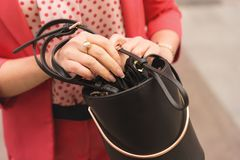 A woman in fashionable clothes of the color of the year 2019 living coral holds in hands with French manicure a black handbag. Fas stock images