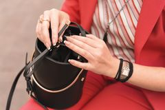 A woman in fashionable clothes of the color of the year 2019 living coral holds in hands with French manicure a black handbag. Fas stock image