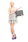 Woman in fashionable dress holding a movie clap. Full length portrait of a woman in fashionable dress holding a movie clap isolated on white background Royalty Free Stock Images