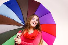 Woman standing under multicolored umbrella Stock Images
