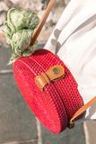 Woman with fashionable stylish red rattan bag and silk scarf outside. Tropical island of Bali, Indonesia. Rattan handbag. Woman with fashionable stylish rattan stock photography