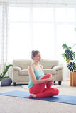 Woman in fashionable tights doing yoga fish pose on yoga mat Stock Photography