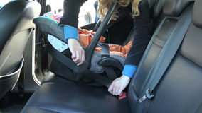 Woman fasten baby safety chair with belt on car back seat. 4K. Woman fasten baby safety chair with infant child on back leather car seat with safety belt and stock video