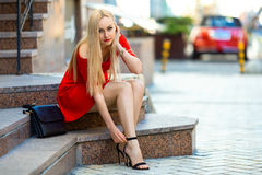 Woman fasten her shoes with high heels. Stock Image