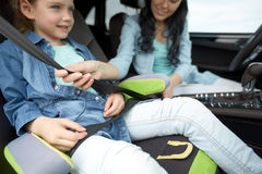 Woman fastening child with safety seat belt in car. Family, transport, road trip and people concept - happy women fastening child with safety seat belt in car stock image