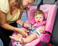 Woman fastening her son on a baby seat Royalty Free Stock Images