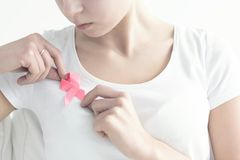 Woman fastening a pink ribbon. Close-up of woman fastening a pink, breast cancer ribbon to a white blouse royalty free stock photography