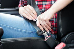 Woman fastening seat belt in car. Close up of female hands fastening seat belt in car. Safety driving concept Royalty Free Stock Photo