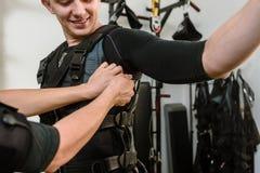 Woman fastening vest. Woman fastening electro muscular stimulation vest on man stock photo