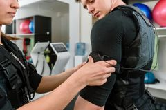 Woman fastening vest. Woman fastening electro muscular stimulation vest on man royalty free stock image
