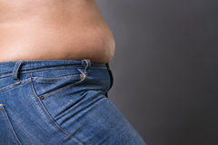 Woman with fat abdomen in blue jeans, overweight female stomach, stretch marks on belly closeup Royalty Free Stock Image