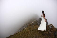 Woman fearing the unknown. Young bride in long white dress on mountain top fearing the fog and the unknown Stock Photo