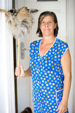 Woman with feather dusters. Charwoman standing with feather dusters in her hand royalty free stock photography