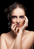 Woman with feather and goth make up on black background Royalty Free Stock Images