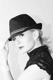 Woman in fedora hat. Beautiful blonde woman in fedora hat, sideways with head turned looking at you the viewer, in black and white Royalty Free Stock Photography