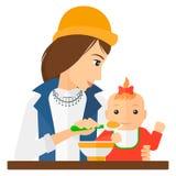 Woman feeding baby Royalty Free Stock Image