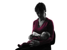 Woman feeding bottle baby  silhouette Stock Photos