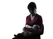 Woman feeding bottle baby  silhouette. One caucasian women feeding bottle baby   silhouette on white background Stock Photos