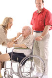 Woman feeding elderly man in wheelchair. Isolated on a white background Stock Image
