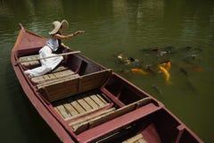 Woman feeding goldfish at a large pond Royalty Free Stock Photos