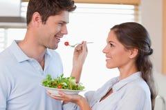 Woman feeding her husband Royalty Free Stock Photos