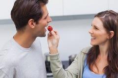 Woman feeding her husband cherry tomato Royalty Free Stock Image