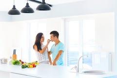 Woman feeding her man in their kitchen stock photo