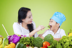 Woman feeding her son with vegetables Royalty Free Stock Photos