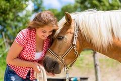 Woman feeding horse on pony farm Stock Photography