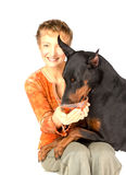 Woman feeding hungry pet dog by red caviar. Isolated on white Stock Photography