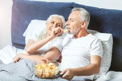 Woman feeding husband with chips stock photos