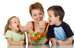 Woman feeding kids with vegetables Royalty Free Stock Photos