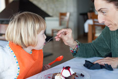 Woman feeding little kid with spoon chocolate cake Royalty Free Stock Images
