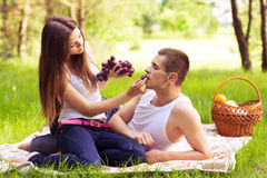 Woman feeding man grapes Stock Image