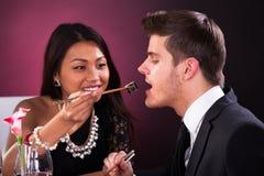 Woman feeding man in restaurant Stock Image