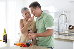 Woman Feeding Pepper To Man In Kitchen Royalty Free Stock Image