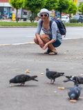 Woman feeding pigeons birds Stock Photography