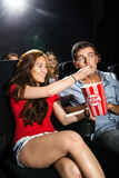 Woman Feeding Popcorn To Boyfriend In Theatre Stock Photo