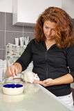 Woman feeding a rat at veterinarian. A beautiful woman in her thirties feeding a domestic rat on an operating table at a veterinarian Stock Photo