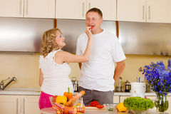 Woman feeds her husband with vegetables. Young pregnant women feeds her husband with vegetables at kitchen royalty free stock photography