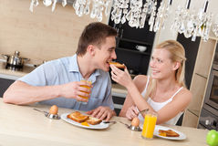 Woman feeds his husband with breakfast in the kitchen Stock Images