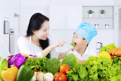 Woman feeds his son with salad. Healthy young women feeds his son with vegetable salad in the kitchen at home Stock Photo